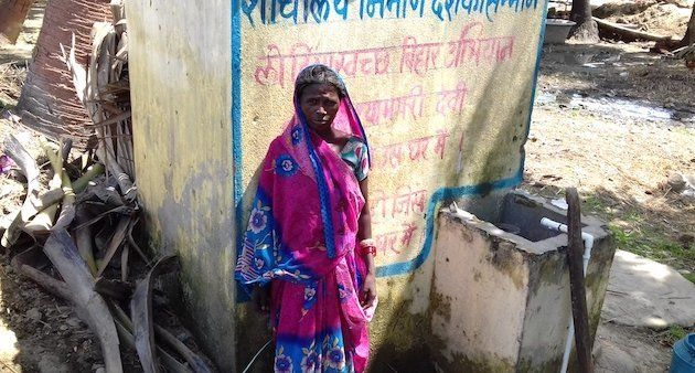 A village woman is standing in front of a newly constructed toilet at her home. (Photo by Mohd Imran