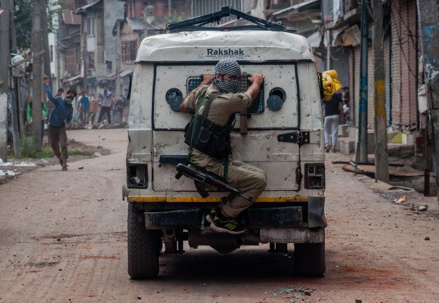 SRINAGAR, KASHMIR, INDIA - AUGUST 30, 2016: An Indian policeman chases Kashmiri Muslim protesters throwing...