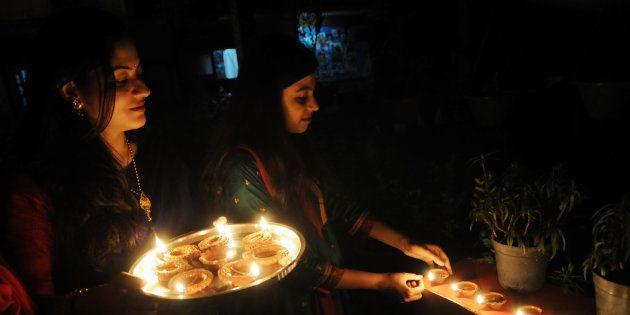 BHOPAL, INDIA - NOVEMBER 10: A woman lighting diya lamps and enjoying Diwali festivities on November 10, 2015 in Bhopal, India.