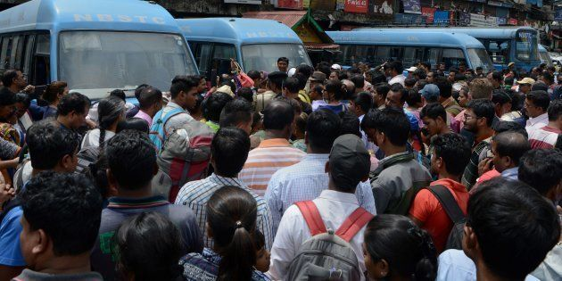 Indian travellers wait for government-provided buses following clashes between police and protesters...