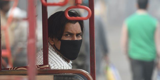 A battery-run tricycle rickshaw operator wearing mask waits for commuters amid heavy smog in the old...