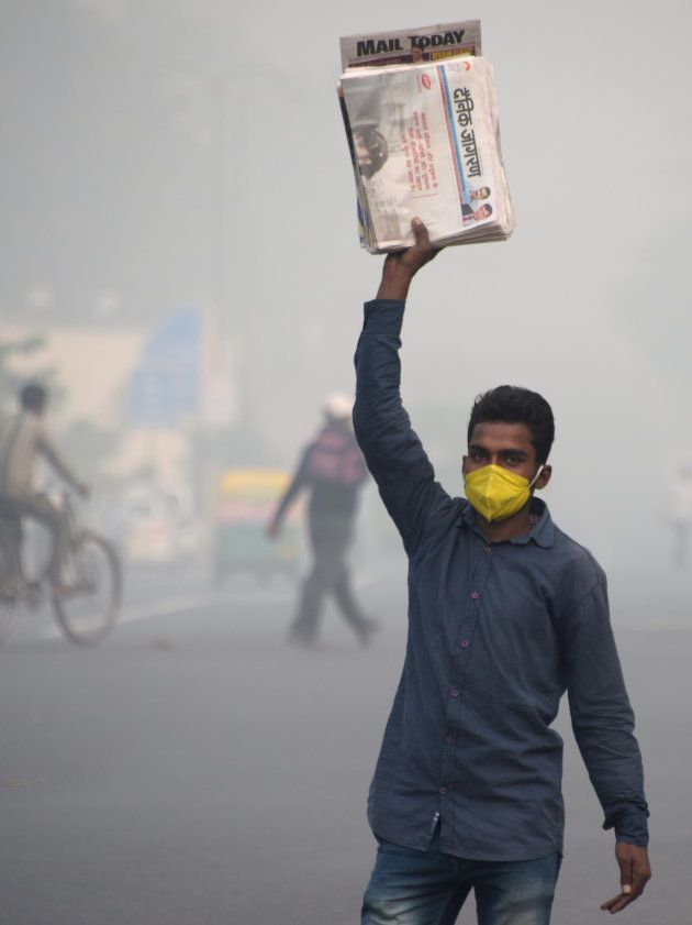 This photo taken on November 9, 2017 shows an Indian newspaper seller wearing a protection mask as he...