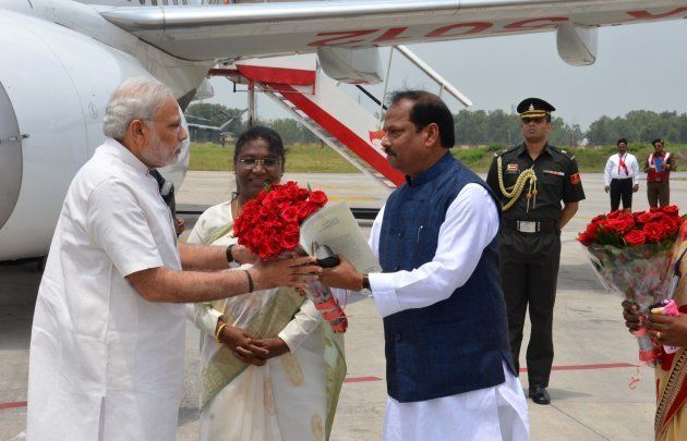 Indian Prime Minister Narendra Modi (L) is received by Chief Minister of Jharkhand Raghubar Das (R) as...