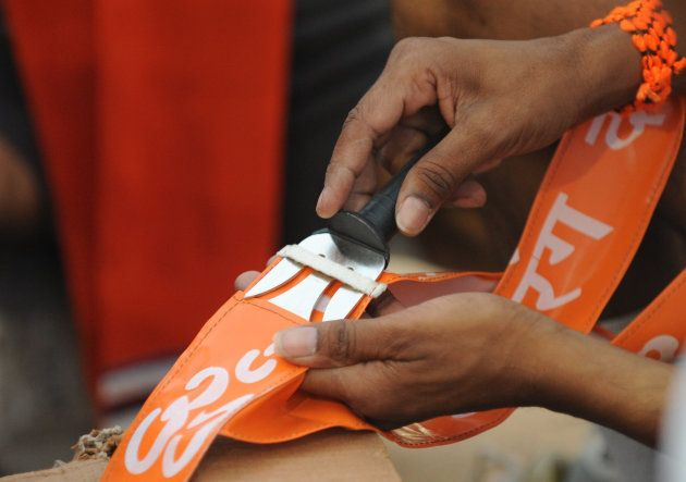 A Bajrang Dal instructor keeps a 'Trishul' or 'Trident' inside a special pocket with a symbol of Hindu Religion 'Aum' printed, to be given to the Bajrangdal volunteers on the last day of a 7 day youth camp at The Koteshwar Swaminarayan Gurukul on the outskirts of Ahmedabad on May 20, 2012.