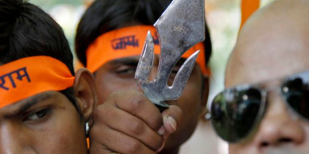 Members from the hardline Hindu groups, Bajrang Dal and Vishwa Hindu Parishad (VHP), hold a trident during...