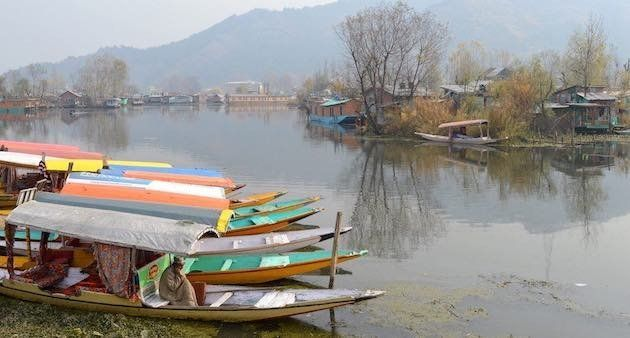 A boatman in Dal Lake warms himself with a fire pot under his pheran cloak. (Photo by Athar