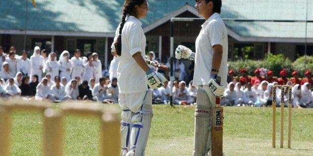 Two Kashmiri batswomen discuss during a cricket match at the Women's College in Srinagar, 13 September