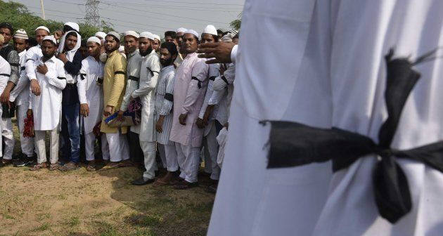 Muslim villagers offer prayers wearing a black band on the occasion of Eid-Ul-Fitr as mark of a silent...