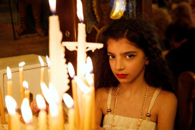 A girl stands near candles inside Al-Saleeb church during Palm Sunday in Damascus, Syria on April 9, 2017.