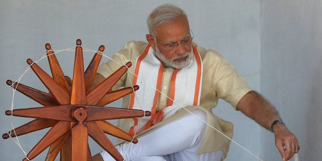 India's Prime Minister Narendra Modi spins cotton on a wheel during his visit to Gandhi Ashram in Ahmedabad,...