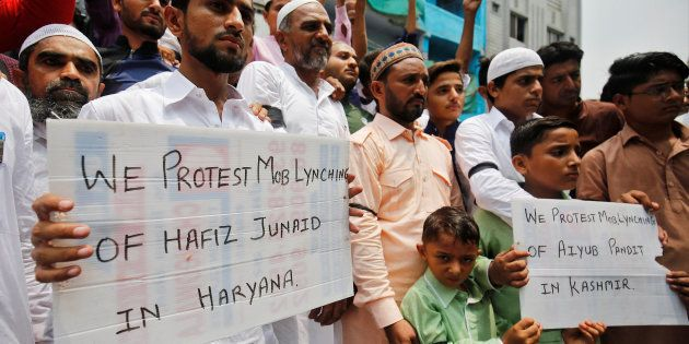 Muslims hold banners as they protest against the recent cases of mob lynching of Muslims who were accused...