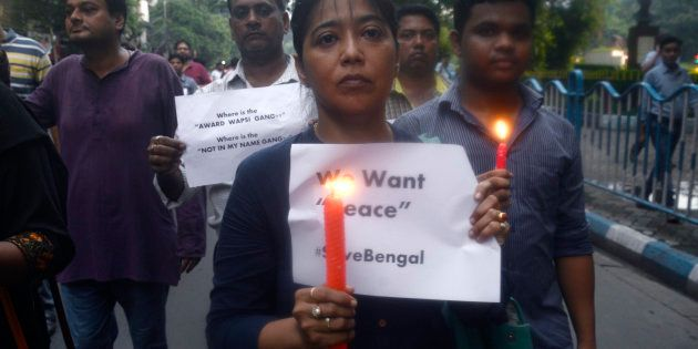 A group of activist participates in a candle light vigil against recent communal violence at Baduria...