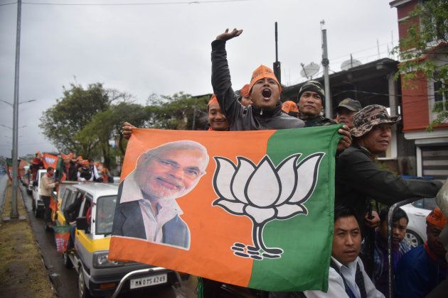 Supporters of the Bharatiya Janata Party (BJP) wave their flags as they celebrate state assembly elections...