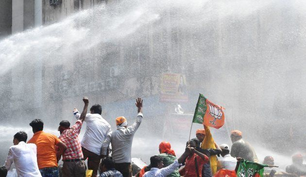 {olice fire a water cannon at activists of the Bhartiya Janata Party (BJP) next to the state police headquarters...