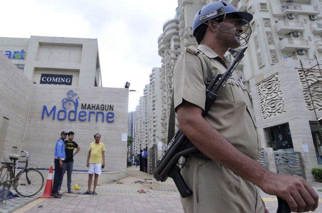 NOIDA, INDIA - JULY 12: Policemen stand guard outside a housing society, Mahagun Moderne in Noida Sector,...