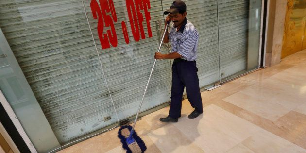 A worker mops the floor in front of a closed shop inside a MGF Metropolitan mall in New Delhi February...