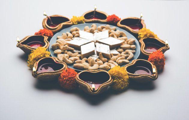 Diwali food Rangoli using Kaju Katli sweet along with Clay diya/lamp and marigold flowers arranged in...