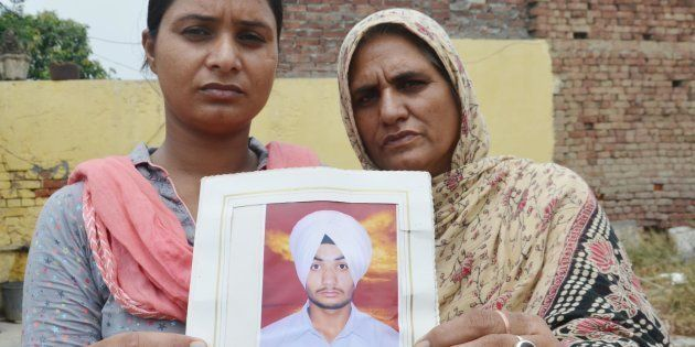 Bhoewal Village residents Gurpinder Kaur (L), along with her mother, hold a photo of her brother Manjinder...