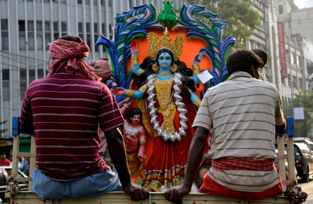 Indian laborers transport an image of Hindu goddess Kali, on a truck ahead of Kali Puja festival in Kolkata,...