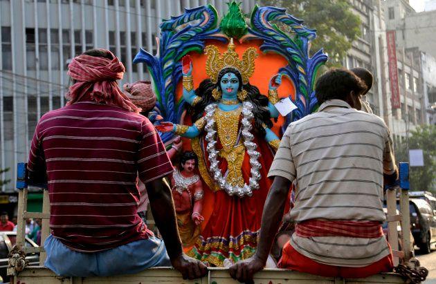 Indian laborers transport an image of Hindu goddess Kali, on a truck ahead of Kali Puja festival in Kolkata, India, Sunday, Nov. 8, 2015. Kali Puja will be celebrated on Nov. 10. (AP Photo/ Bikas Das)
