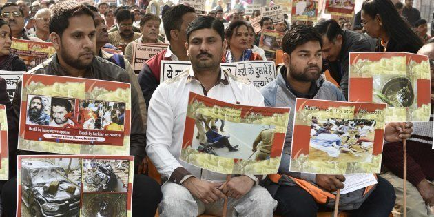 Supporters and workers holding placard during the protest against brutal attack on RSS-BJP workers in...