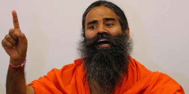 Indian yoga guru Baba Ramdev gestures as addresses the media during a news conference in Ahmedabad, India,...