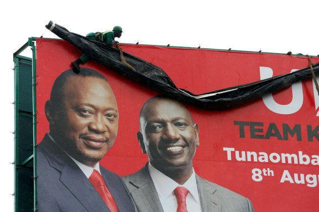 A worker hangs ontop of an election campaign billboard displaying Kenya's President Uhuru Kenyatta (L)...