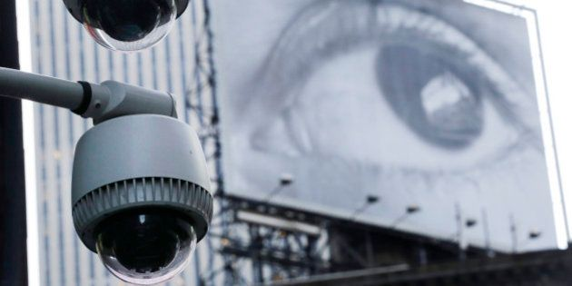 Security cameras are mounted on the side of a building overlooking an intersection in midtown Manhattan....
