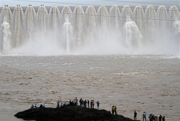 Picnickers stand in front of the overflowing Sardar Sarovar Narmada dam in Kavadia, 194 km south of Ahmedabad,...