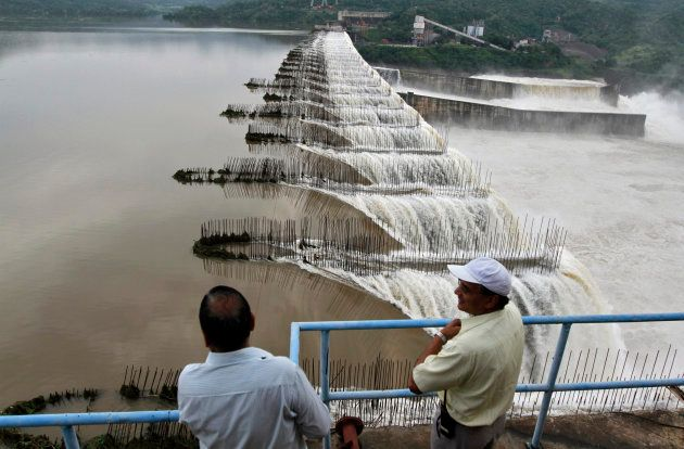Indian officials look at the overflowing Sardar Sarovar Narmada dam in Kavadia, 194 km south of Ahmedabad,...