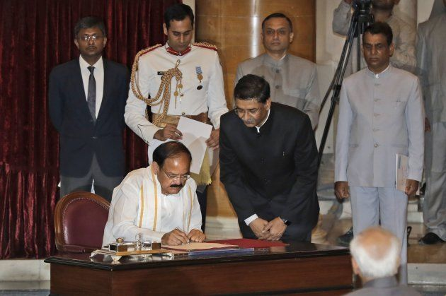 Venkaiah Naidu (L) signs the official book after being sworn in as India's new vice president as outgoing...