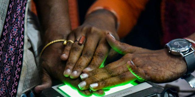 Women scanning fingerprints as an Aadhaar registration