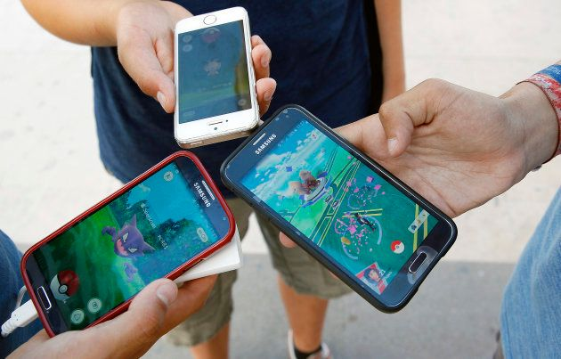 Kids show their smartphones with Pokemon