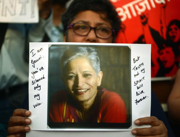 An Indian protester holds a placard in a rally condemning the killing of journalist Gauri Lankesh, in...