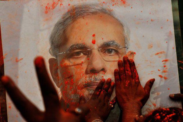 BJP supporters celebrate Holi with Prime Minister Narendra Modi's photograph.