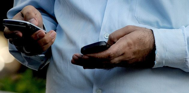 An Indian officegoer checks a text message on his mobile phone in Mumbai on September 27,