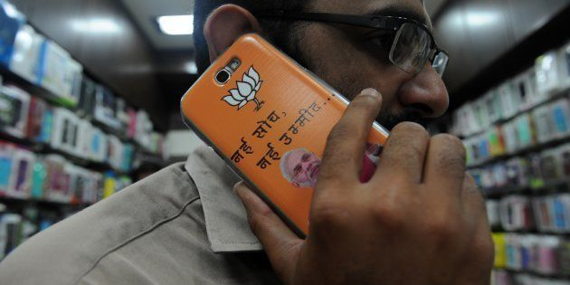 An Indian shopkeeper speaks on his mobile phone adorned with a cover featuring Bharatiya Janata Party's...