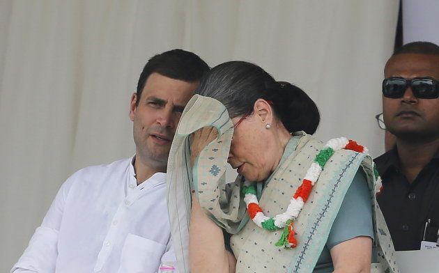 India's Congress party president Sonia Gandhi wipes her sweat as party'™s vice-president Rahul Gandhi...