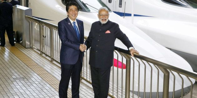 Indian Prime Minister Narendra Modi (R) and Japan's Prime Minister Shinzo Abe pose in front of a Shinkansen...