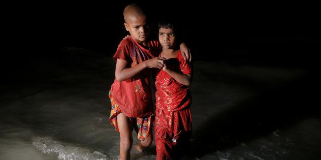 Rohingya refugee sisters, who just arrived under the cover of darkness by wooden boats from Myanmar,...