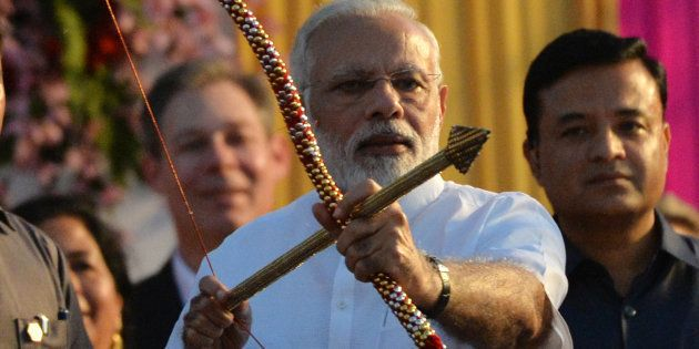 Indian Prime Minister Narendra Modi holds a bow and arrow at an event ahead of the burning of the effigy...