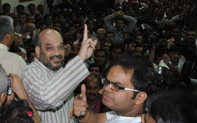 Indian politician and former Gujarat minister Amit Shah (L) and his son Jay celebrate on his arrival...