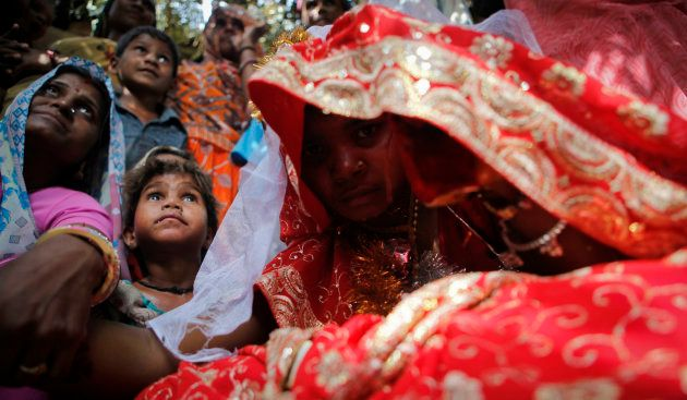 Child bride Krishna,11, sits during a marriage ceremony at her husband's home in a village near Kota...