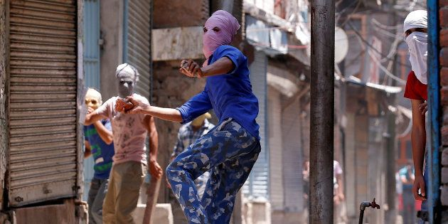 A masked protetser throws pieces of bricks and stones towards Indian police officers during a clash on...