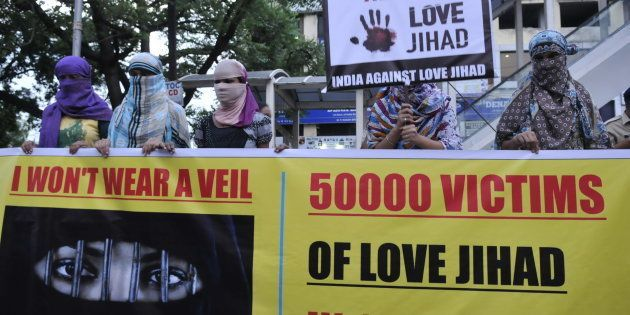 Women associated with India Against Love Jihad hold placards and form a human chain to protest against...