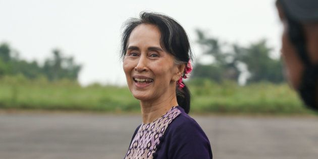 Myanmar State Counselor Aung San Suu Kyi smiles as she walks from a military helicopter after arriving...