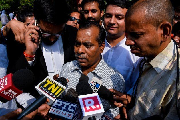The father of Indian gangrape victim 'Nirbhaya' addresses media representatives as he leaves The Supreme...