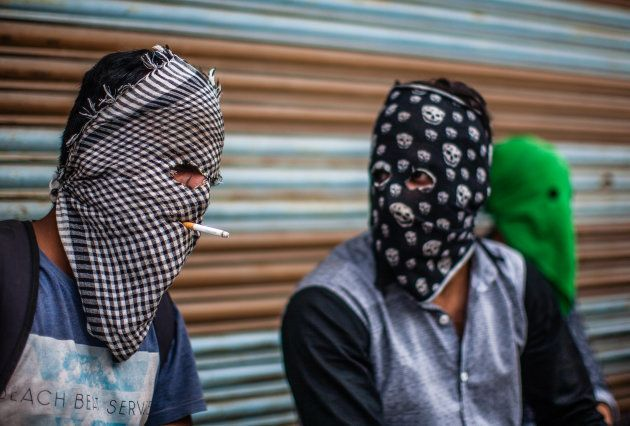 A masked Kashmiri Muslim protester puffs on a cigarette as a fellow protester talks to him during a protest...