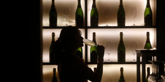 A woman poses with a glass of wine at a tapas bar in Mumbai March 9,