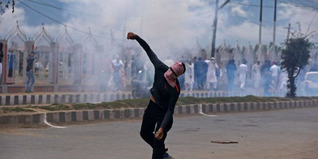 A demonstrator hurls a stone amid smoke from a tear gas shell fired by the Indian police during clashes...